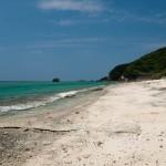 Vit strand och blått vatten