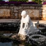 Staty föreställande en kvinna som tvättar kläder sittandes på knä vid vattnet